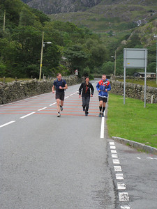 Partly by by sliding down the mountain seen here on my behind, I managed to keep up with frontrunners Kate and Steve. Here the three of us run into the first checkpoint at Nant Peris, arriving at 07:07.