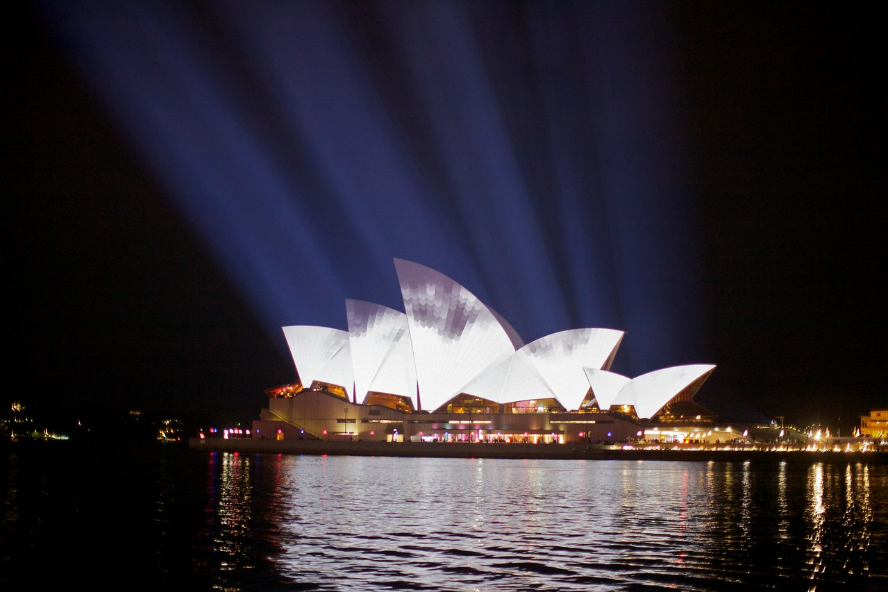 Beams of light cast by massive projectors on the Overseas Passenger Terminal onto the Opera House.