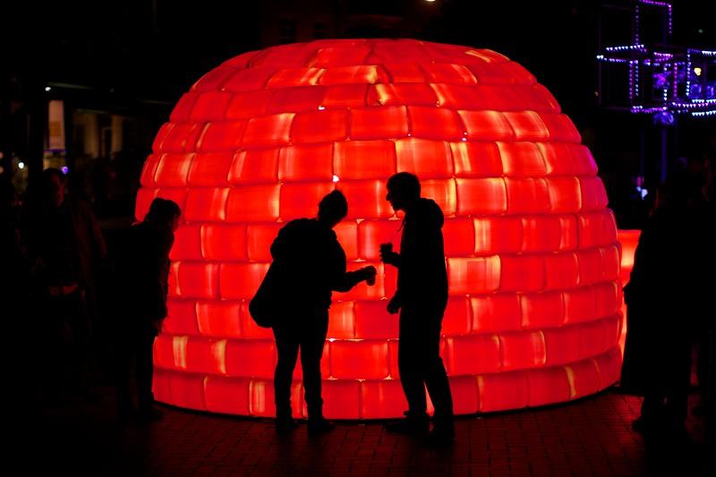 Visitors examine a big red plastic igloo.