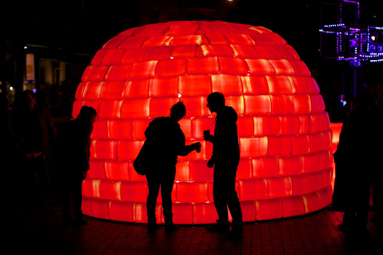 Visitors examine a big red plastic igloo.