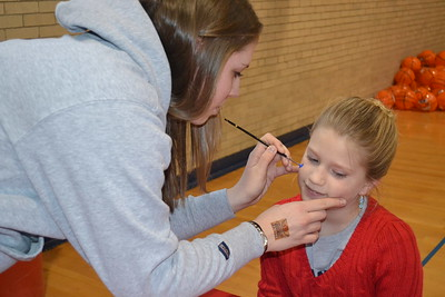 Liz, student volunteer (Eng'15), has artistic talent with facepainting.