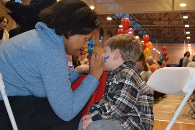 Deidre, student volunteer (C'13) gives a youngster some Penn spirit.