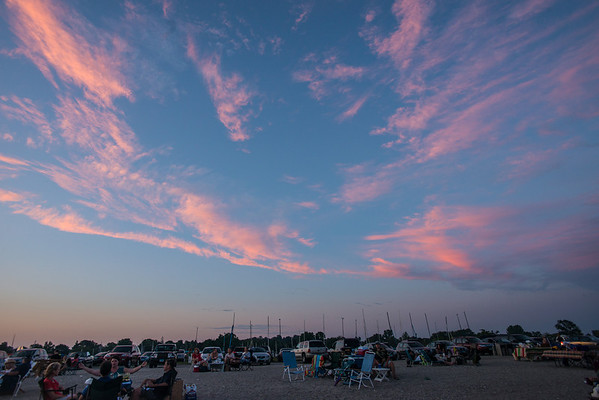 Sky starting to become pinkish and lots of people enjoying the beautiful weather, having picnics at the beach!