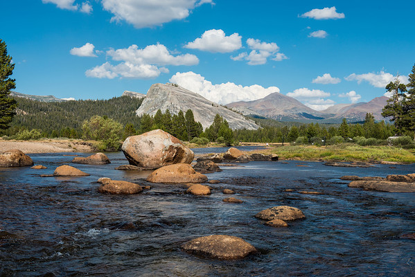 The Tuolumne River bends around boulders as Lembert Dome looms in the background.