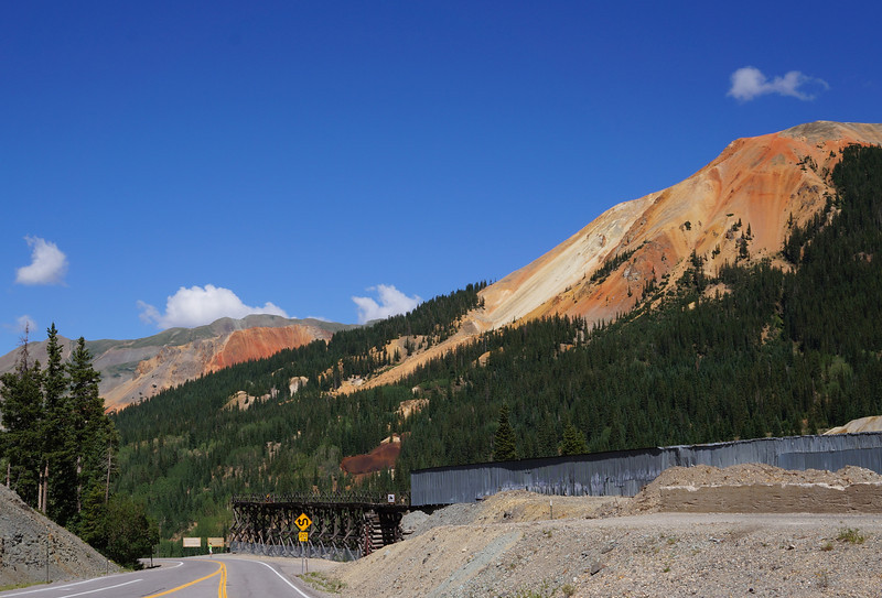 """With both gold and silver having been discovered in the area, man really left his mark on this view of Red Mountain.  Back in the 1870s, mines were common in southwest Colorado with lots of activity.  As one of the larger mines in the San Juan Mountains, the Idarado Mine contains almost 100 miles of underground tunnels.  Miners would enter here at the Treasury Tunnel and ride underground trams to their work stations.  In its time, the mine produced 4 million ounces of gold, 21 million ounces of silver, and 12 million tons of lead, zinc, and copper – making a significant contribution to the industrial revolution."" - <a href=""http://www.coloradocaptures.com/2010/01/miners-mark-on-red-mountain-red-mountain-pass/"">http://www.coloradocaptures.com/2010/01/miners-mark-on-red-mountain-red-mountain-pass/</a>"