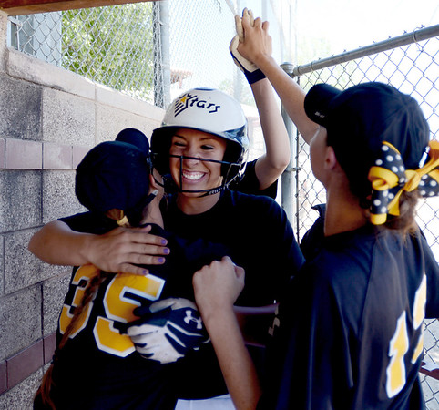 Mallory Paulson, center, of the Colorado Stars hit a home run to help her team beat the California Stars and qualify for nationals.  She is congratulated by Michaela Good, left, and Sara Good in the dugout.<br /> June 17, 2012