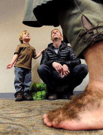 "Eli Billiings, 4, and his father, Stephen, listen to Bilbo Baggins (Clay Evans) as seen through Baggins' hairy feet.<br /> The Grey Havens Group celebrated a Hobbit Holiday at the  Longmont Public Library on Sunday with readings, games and activities.<br /> For a video of the Hobbit Holiday, go to  <a href=""http://www.timescall.com"">http://www.timescall.com</a>.<br /> Cliff Grassmick  / December 9, 2012"