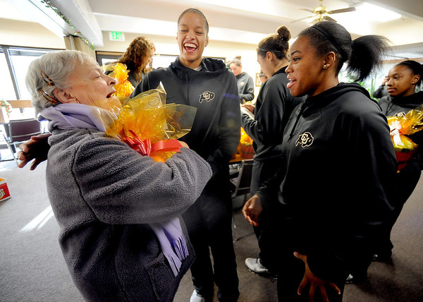 "Kay McLaughlin, left, a resident at Canyon Pointe, appears thrilled to get a holiday basket from Arielle Roberson, center, and Ashley Wilson,  both CU basketball players.<br /> The CU women's basketball team and coaches joined up with local nonprofits on Saturday, December 8 to deliver holiday fruit baskets to over 900  seniors in Boulder County. For a video of the event, go to  <a href=""http://www.dailycamera.com"">http://www.dailycamera.com</a>.<br /> Cliff Grassmick  / December 8, 2012"