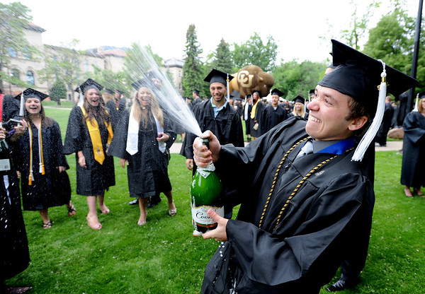 "Russ McDermott blows off some champagne on Norlin Quad before the CU graduation ceremony of Friday.<br /> The ceremony will honor candidates for 6,237 degrees, including 4,830 bachelor's degrees, 994 master's degrees, 162 law degrees and 251 doctoral degrees for spring and summer.<br /> The number of degree applications for the University of Colorado is the largest in the school's history, and comes four years after the record-setting freshman class of fall 2008. That year, 5,833 freshmen enrolled, exceeding the previous record-setting class of 2006 that enrolled 5,617 freshmen. For more photos and a video, go to  <a href=""http://www.dailycamera.com"">http://www.dailycamera.com</a>.<br /> Cliff Grassmick / May 11, 2012"