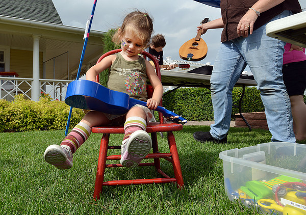Stella High, 2, tries playing a blue ukulele during Summer Sundays at the Brunner Farmhouse on Sunday.<br /> <br /> July 8, 2012<br /> staff photo/ David R. Jennings