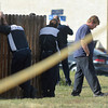 Employees  of East of Sweden Saab repair stand near a fence at 155 Commerce St. after a fellow employee was shot and killed in Broomfield.<br /> October 12, 2012<br /> staff photo/ David R. Jennings