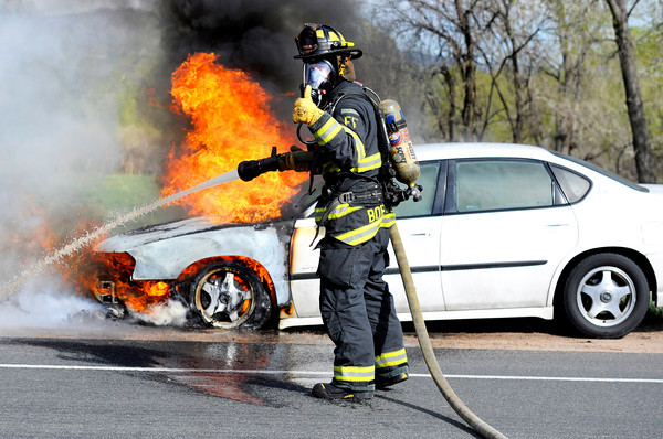 Boulder Fire Rescue firefighter Ryan Boersma tells the engineer to increase the water pressure while trying to extinguish a car fire at the intersection of Valmont Road and Butte Mille Road in Boulder on Thursday, April 19.<br /> Jeremy Papasso/ Camera