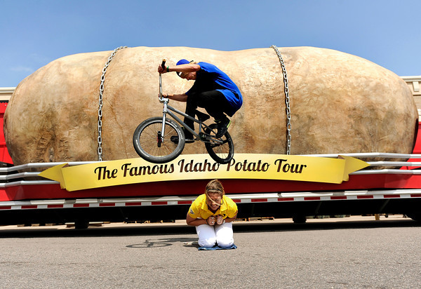 """Tour ambassador Kaiti Frickey cringes as Taylor Bounds, 19, of Broomfield, jumps her with his bmx bike while riding on his lunch break from work in front of the giant potato during The Famous Idaho Potato Tour on Wednesday, April 11, at the King Soopers shopping center on 136th Avenue in Broomfield. For a video about the giant potato truck go to  <a href=""""http://www.dailycamera.com"""">http://www.dailycamera.com</a><br /> Jeremy Papasso/ Camera"""