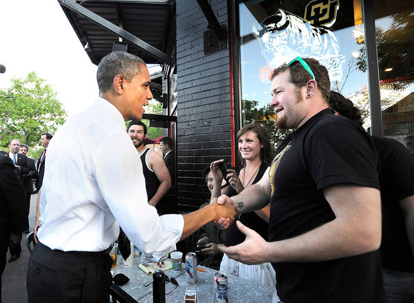 President Barack Obama shakes hands with Dan Williams, of Boulder, outside of The Sink restaurant on University Hill in Boulder in an unexpected detour from the Coors Events Center before his speech on Tuesday April 24, 2012. Obama took a box of pizza to his motorcade. See photos and video of the President's first visit to Boulder in April<br /> Photo by Jeremy Papasso April 24, 2012