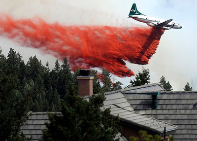 A heavy tanker drops fire retardant next to a home while fighting the Flagstaff wildfire on Tuesday, June 26, in Boulder. For a video of the fire go to www.dailycamera.com Jeremy Papasso/ Camera