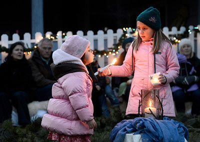 Celia Reynolds, 6, at right, holds a candle while her sister Julia Reynolds, 3, tries to blow it out on Friday, Dec. 7, at a winter solstice gathering at the Spiral Garden in Boulder. For a video of the Spiral Garden event go to www.dailycamera.com Jeremy Papasso/ Camera