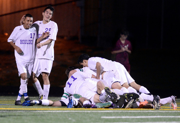 "Boulder High School's Luis Castruita, left, gets a hug from teammate Pancho Valdivieso as their team forms a hog pile after scoring the winning goal during a playoff game against Chatfield High School on Monday, Oct. 29, at Recht Field in Boulder. Boulder won the game 3-2. For more photos of the game go to  <a href=""http://www.dailycamera.com"">http://www.dailycamera.com</a><br /> Jeremy Papasso/ Camera"