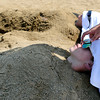 Chris Miller, 15, front, gets his nose itched by Kirsy Kunard, while buried in the sand with his friend Beau Phenicie, back, on Thursday, July 12, at the Boulder Reservoir. Swimming at the reservoir is currently restricted due to high levels of bacteria.<br />  Jeremy Papasso/ Camera