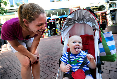 Emily Cooper, of Boulder, left, laughs as her one-year-old son Jonah gets his first taste of ice cream while at the Glacier Home Made Ice Cream & Gelato stand on Thursday, June 7, on Pearl Street in Boulder. Jeremy Papasso/ Camera