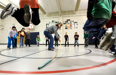 First grade students jump over a bamboo stick while playing a game with physical education teacher Amy Hancock, center, on Tuesday, Jan. 10, at Whittier Elementary School in Boulder. The Boulder Valley School Board is looking into possible solutions to the school's overcrowding problem. Jeremy Papasso/ Camera