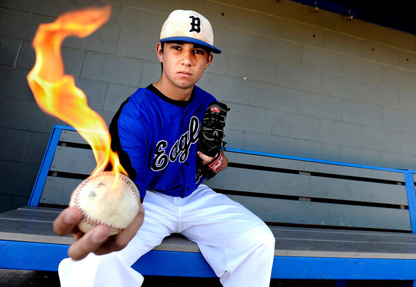 Broomfield High School's Brandon Bailey holds a flaming baseball on Monday, June 11, inside a dugout of the baseball field at Broomfield High School. Bailey has been clocked at speeds up to 95 m.p.h. while pitching.<br /> Jeremy Papasso/ Camera