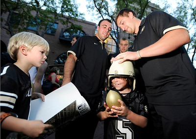 University of Colorado football players Keegan Lamar, right, and Jesse Hiss sign the helmet of Zander Carlyle, 6, while Grayson Strauss, 5, at left, waits to have his poster signed on Friday, Aug. 31, during the CU pep rally on Pearl Street in Boulder. For more photos and video of the pep rally go to www.dailycamera.com Jeremy Papasso/ Camera