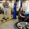 Chief Carhugger Ryan Ferrero holds his hand over his face while Jenny Strovink demonstrates how to change a tire during a Women Wine and Wrenches class on Thursday, Nov. 8, at the Green Garage near 55th and Pearl.<br /> Jeremy Papasso/ Camera
