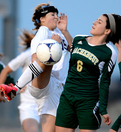 Holy Family's Maddie Kuzik (left) tries to knee the ball into the goal on a corner kick while being blocked Machenbuef's Katie Schaffer (right) during their soccer game at Holy Family High in Broomfield, Colorado March 27, 2012. CAMERA/MARK LEFFINGWELL
