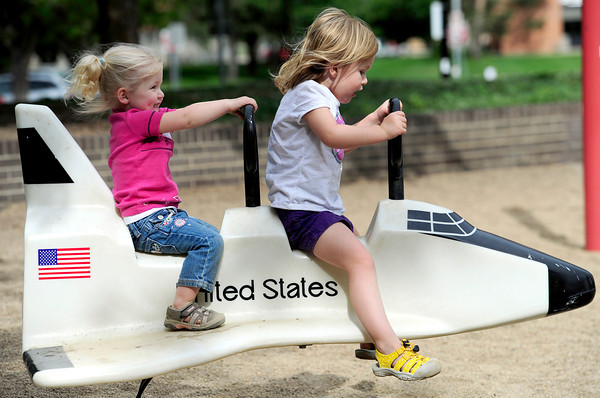 Molly Sturtz (left), 2, and her sister Brook Sturtz (right), 4, ride the space shuttle at Scott Carpenter Park in Boulder, Colorado May 16, 2012. CAMERA/ MARK Leffingwell