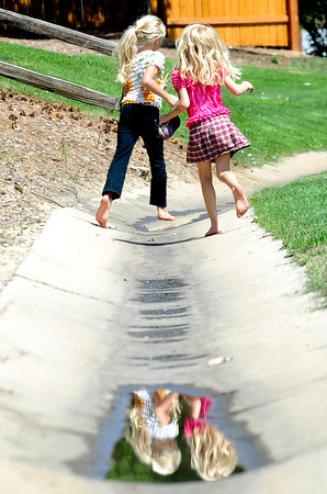Cody Ervin (left), 8, and Alex Ervin (right), 6, head home after playing in the park by themselves in Longmont, Colorado August 8, 2012. DAILY CAMERA MARK LEFFINGWELL