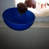 Preparing bowls of rice and beans at the church.  Each day they determine how many children they can feed and allow that number of children inside the church.  Each child brings their own bowl.  There are always children left outside because there is just not enough for everyone.  This child did not make it inside the church.