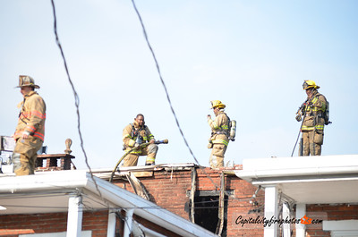 April 20, 2012, Harrisburg, PA - City firefighters overhaul the rear of 1420 N. 2nd Street in the Midtown district after extinguishing a fire damaged that two apartments. Careless smoking sparked a deck fire that extended into the row of occupied dwellings.