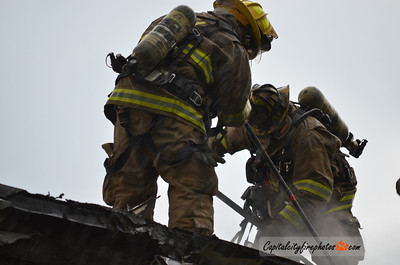 April 21, 2012 - Harrisburg, PA - Firefighters open up the rear roof after extinguishing an afternoon fire that heavily damaged a city duplex. The fire was placed under control in about 25 minutes with no injuries.