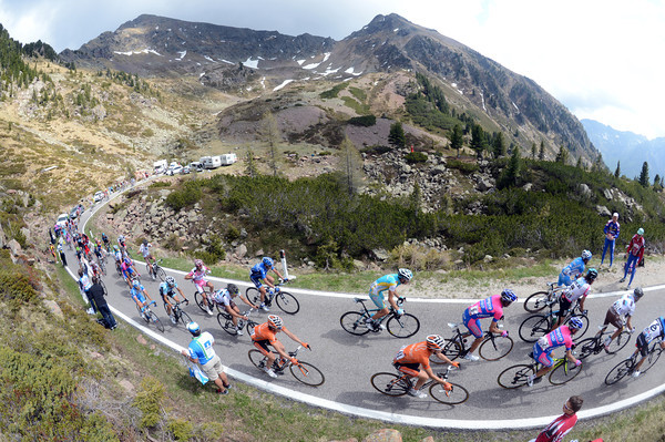 A much smaller peloton crosses the pretty summit of the Passo Manghen...