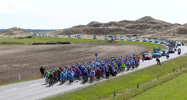 The peloton passes along a causeway separating the sea from the land...