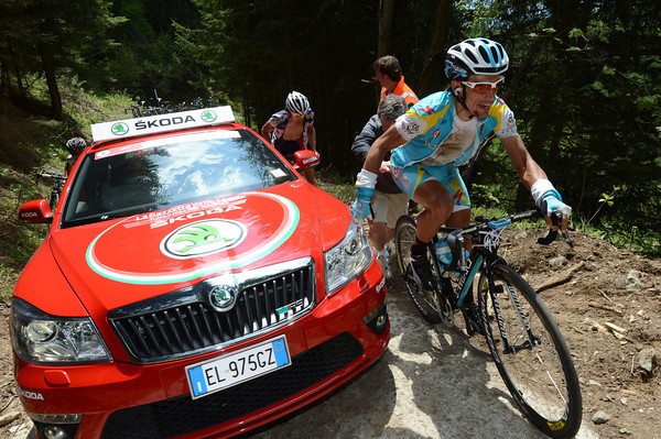 An official car has stalled on the steep ascent, causing havoc for riders like Tiralongo...