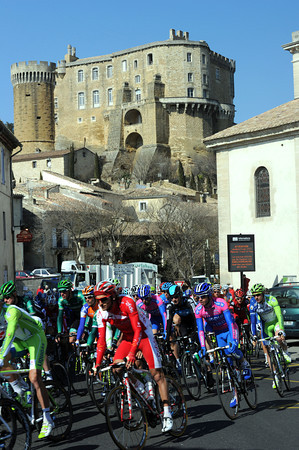 The peloton rolls away from the Chateau at Suze-La-Rousse...