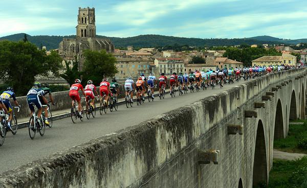 The peloton races across the Pont de Saint-Esprit after about 20-kilometres...