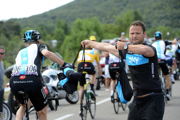 A Sky helper is a study in concentration as he serves his riders their lunch in the feed-zone...