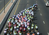 The peloton is straddled across the highway, in-line astern of Team Sky...