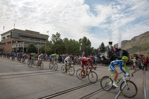 The peloton is strung out in pursuit of the early attack as they pass the Durango Silverton steam locomotive.