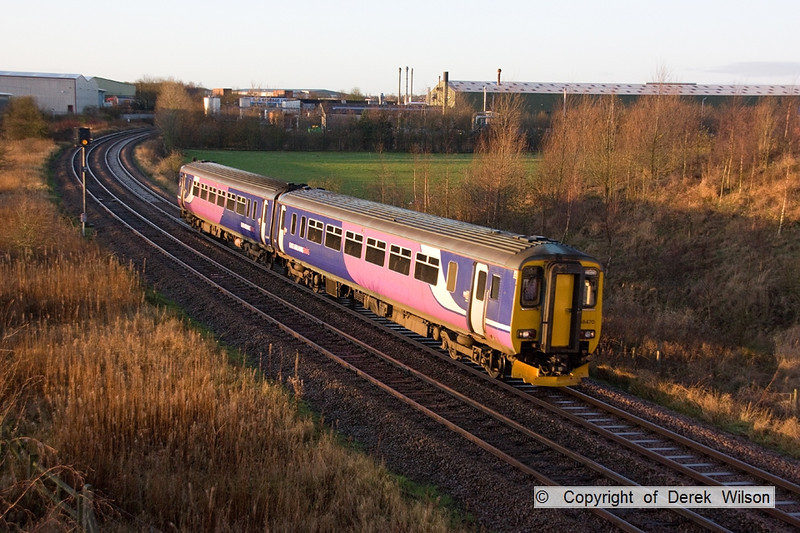 120102-001     Train 2W04, the 08.25 Nottingham-Worksop, formed by class 156 unit no 156470, in Northern Rail livery, with East Midlands Trains branding, captured in early morning sunlight, from the A617 road bridge at Sutton in Ashfield.