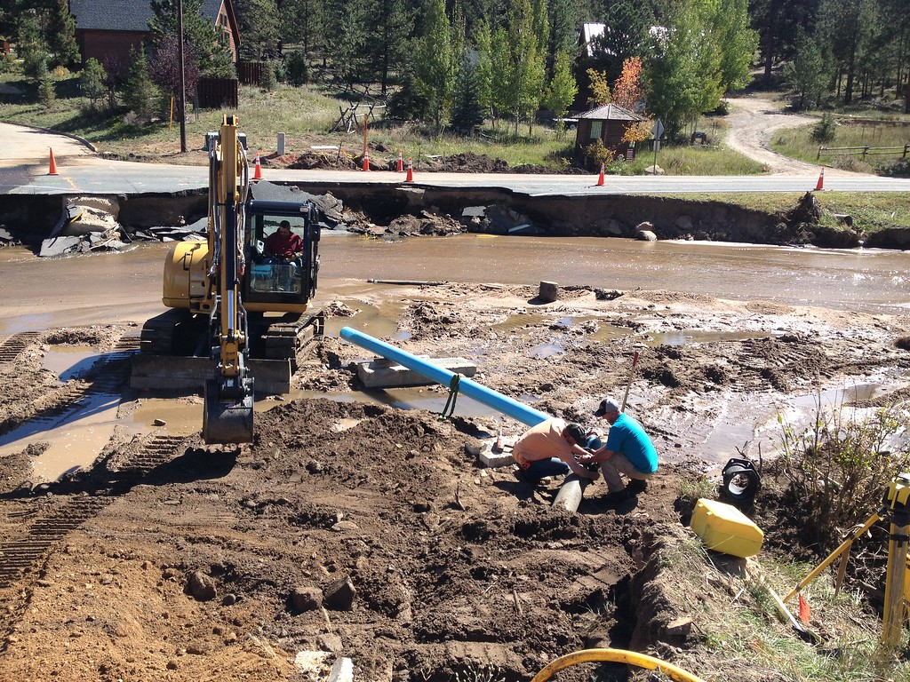 . Construction crews work to rebuild the banks along Fish Creek Road