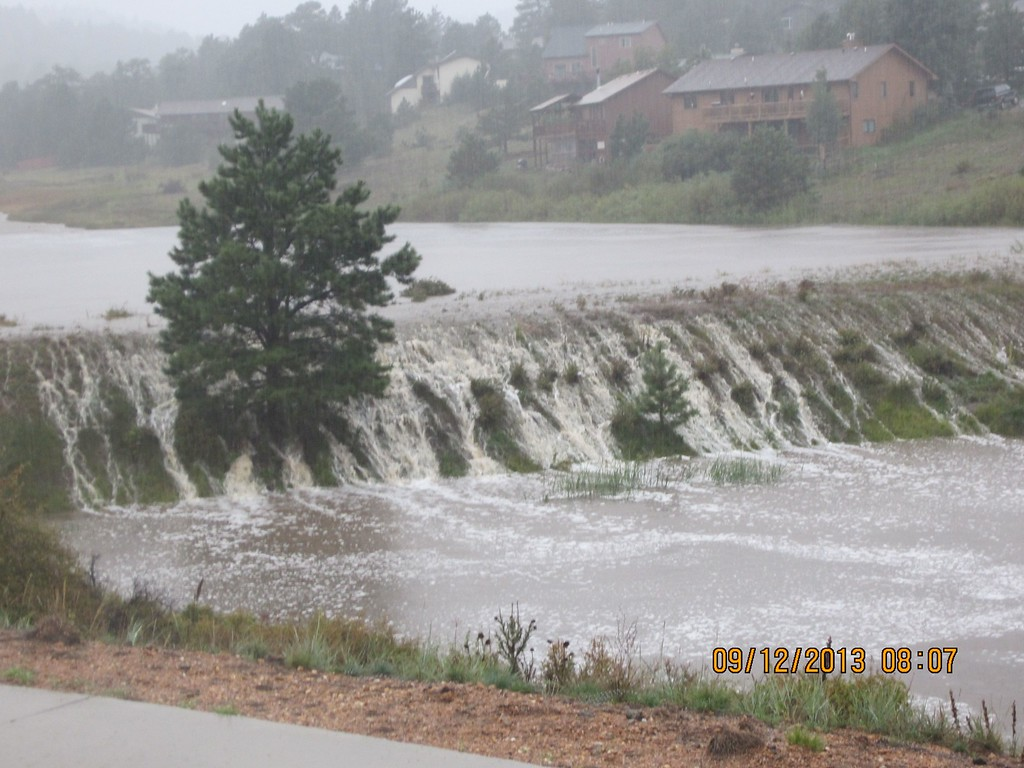 . Courtesy of the Town of Estes Park. Water rushing over the banks of Scott Pond.