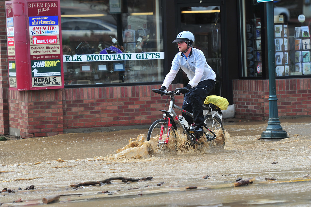. A worker bikes through water trying to get to work on the morning of Sept. 13, 2013