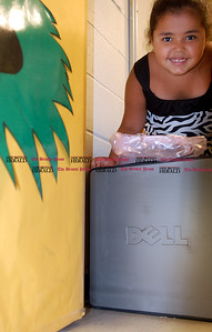 Johnny Burnham | Staff Lili Ortero, a second-grader, smiles as she grabs her Dell Computer Thursday. Select students with perfect attendance during the Smalley Summer Learning Program received Dell desktop computers.
