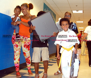Johnny Burnham | Staff Jaqwon Dowd, a third-grader, smiles after receiving a computer for his perfect attandance during a summer learning program at Smalley Academy. His older brother, Javon, helps him carry it out of the school.