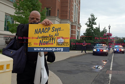 Johnny Burnham | Staff Brian Keith Albert holds up a sign during the rally outside the courthouse Thursday evening.