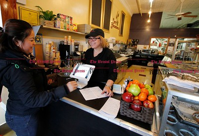 Kevin Bartram | Staff Alice Chiovoloni, right, waits on Oumaphone Siboriboun on opening day at Cafe Beauregard on Main Street in New Britain on Tuesday. The restaurant, owned by Alice and her husband Rob Chiovoloni, is at 2 Main Street.