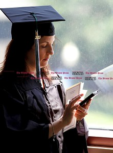 Kevin Bartram | Staff Audrey Betancourt checks her smartphone before the Charter Oak College graduation on Sunday on the campus of Central Connecticut State University in New Britain. Betancourt returned to school after being laid off and was able to compete her Bachelors of Arts degree in one year. Charter Oak offers online degree programs and accelerated completion plans.